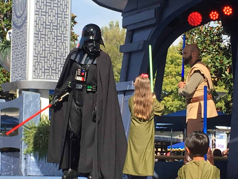 Emma fighting off Darth Vader at Disneyland