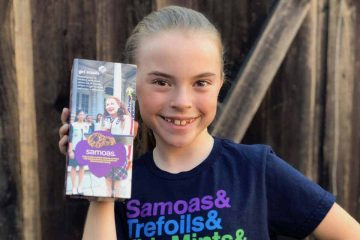 Our girl holding up a box of Samoas