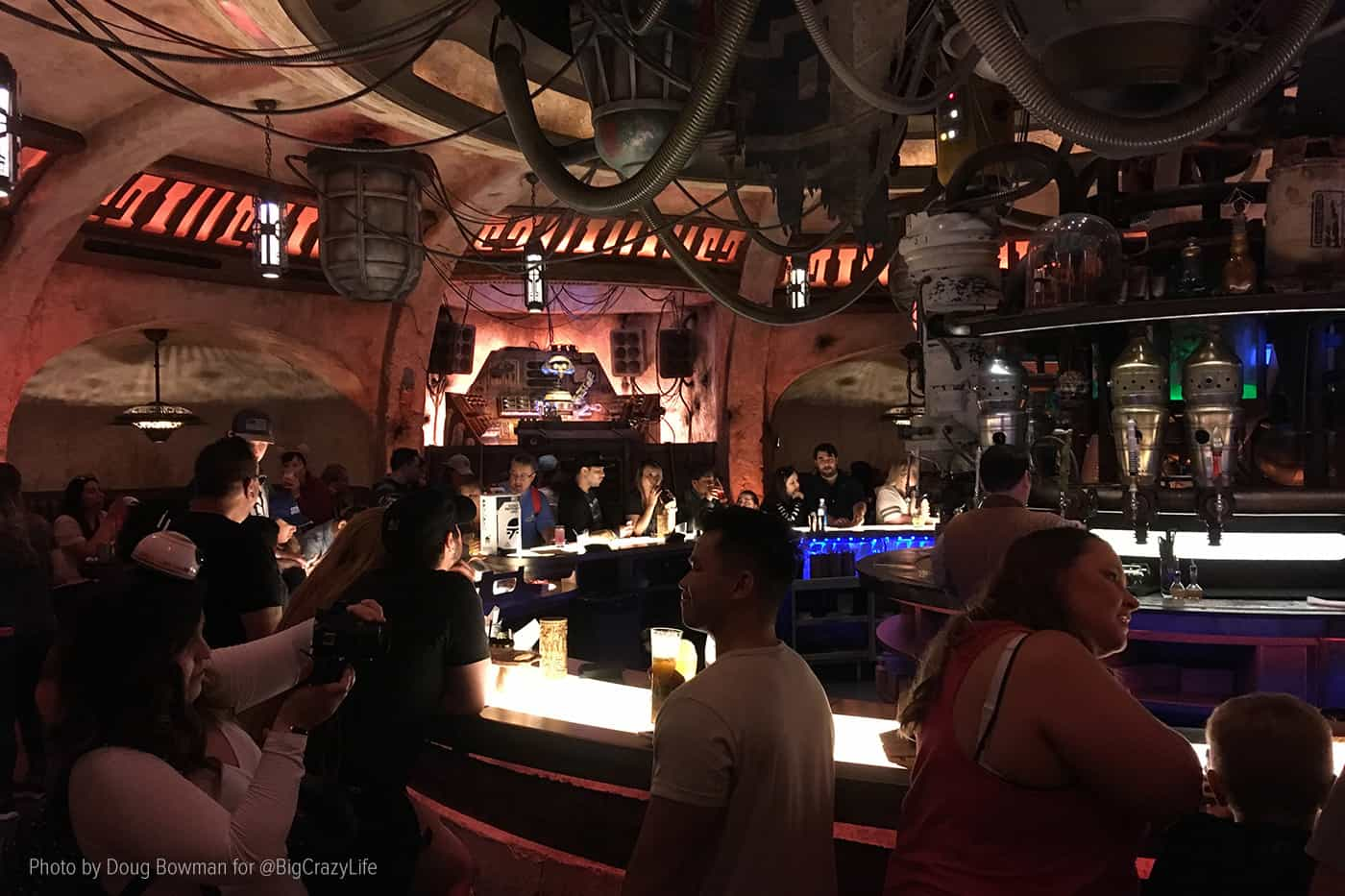 Interior shot of Oga's Cantina with the bar in the foreground and DJ R-3X spinning tunes in the background.