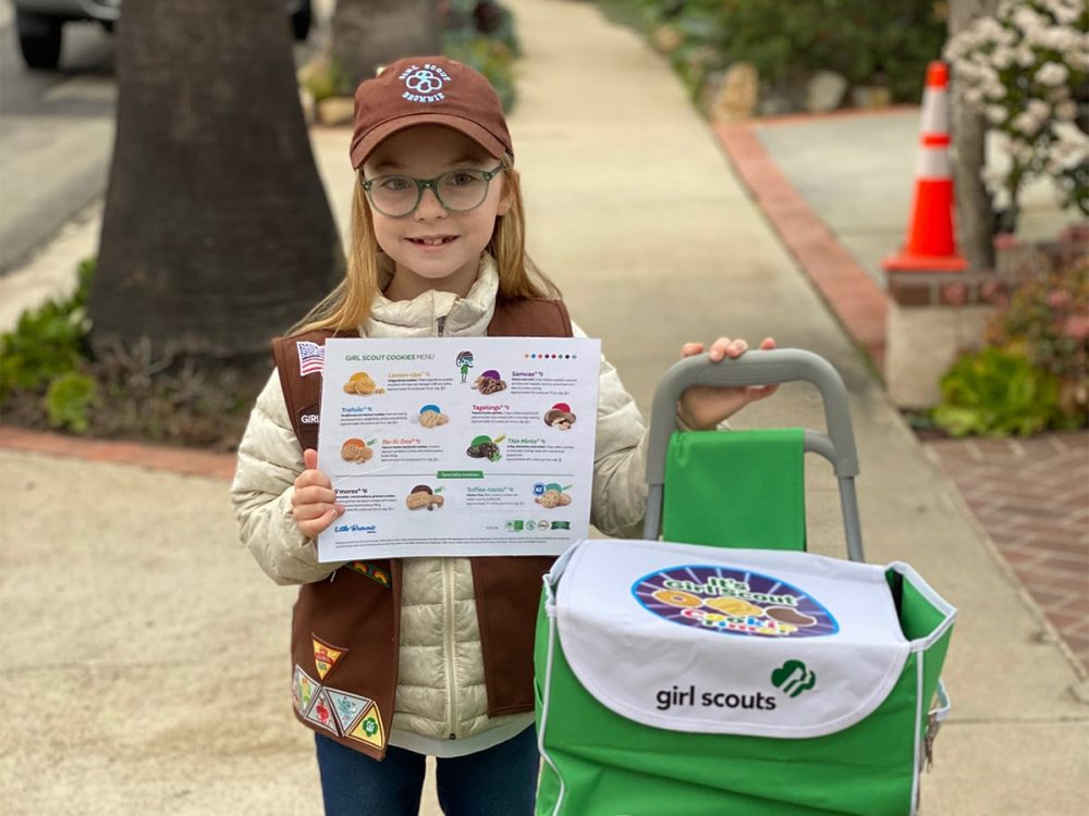Selling Girl Scout cookies with a cart and cookie menu